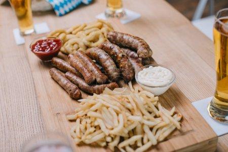 Photo pour Plateau en bois avec saucisses frites, rondelles d'oignon, frites français et sauces près des verres avec de la bière légère dans le pub - image libre de droit