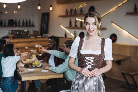 Photo pour Belle serveuse dans le sourire national allemand de costume tout en regardant l'appareil-photo - image libre de droit