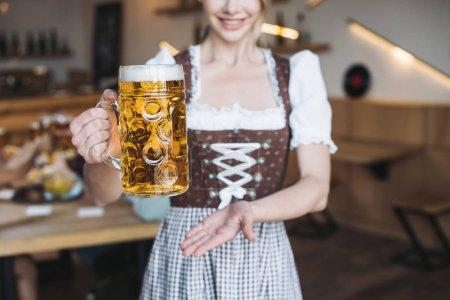 Photo pour Vue recadrée de serveuse dans la tasse nationale allemande de fixation de costume de la bière légère - image libre de droit