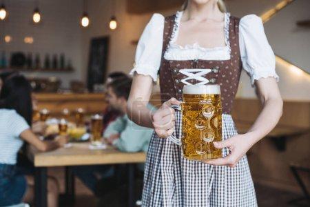 Photo pour Vue patial de serveuse dans la tasse nationale allemande de fixation de costume de la bière légère - image libre de droit
