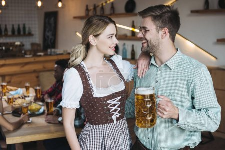 Photo for Attractive waitress in german national costume standing near young man holding mug of light beer - Royalty Free Image