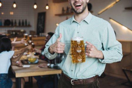 Photo pour Vue recadrée de jeune homme de sourire retenant la tasse de la bière de lager et affichant le pouce vers le haut - image libre de droit