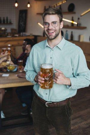 Красивый молодой человек держит кружку светлого пива и улыбается в камеру