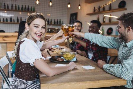 Photo pour Amis multiculturels heureux clignotant des verres de bière légère tout en célébrant octoberfest dans le pub - image libre de droit