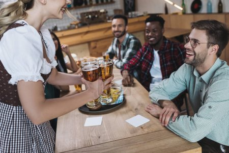 Photo pour Vue recadrée de serveuse retenant des glaces de bière légère près des amis multiculturels - image libre de droit