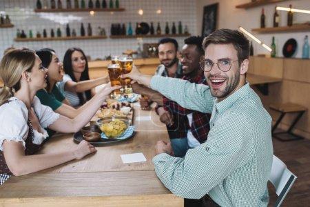 Photo pour Beau jeune homme souriant à l'appareil-photo tout en célébrant l'octoberfest dans le pub avec des amis multiculturels - image libre de droit