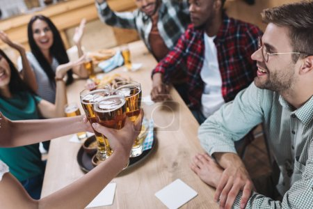 Photo for Partial view of waitress holding glasses of light beer near multicultural friends - Royalty Free Image