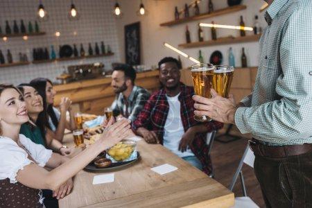Photo pour Vue recadrée de l'homme retenant des glaces de bière légère près des amis multiculturels dans le pub - image libre de droit