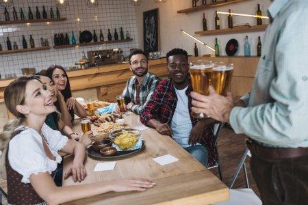 Photo pour Vue partielle de l'homme retenant des glaces de bière légère près des amis multiculturels dans le pub - image libre de droit