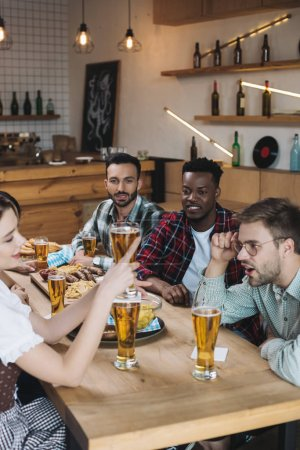 Photo for Cheerful multicultural friends celebrating octoberfest together in pub - Royalty Free Image