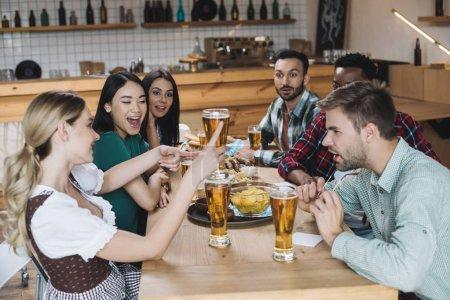 Foto de Amigos multiculturales felices y jóvenes celebrando el festival de octubre juntos en el pub - Imagen libre de derechos