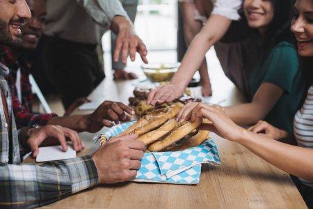 Photo pour Vue recadrée d'amis multiculturels prenant des bretzels savoureux tout en passant du temps ensemble dans le pub - image libre de droit