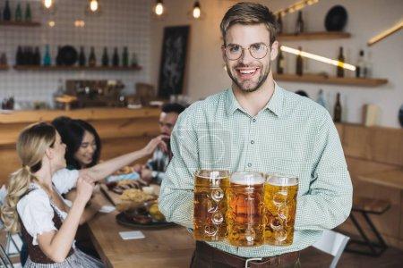 Photo pour Jeune homme beau retenant des tasses avec la bière et souriant à l'appareil-photo - image libre de droit