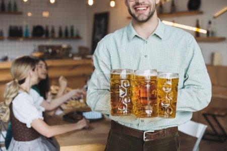 Photo pour Vue recadrée de jeunes hommes retenant des tasses avec la bière et souriant à l'appareil-photo - image libre de droit