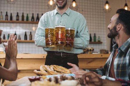 Photo pour Vue recadrée de jeune homme retenant des tasses avec la bière tout en restant près des amis multiculturels dans le pub - image libre de droit