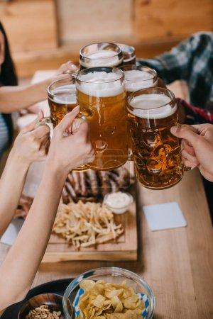 Photo pour Vue partielle des amis clinking tasses de bière tout en célébrant l'octoberfest dans le pub - image libre de droit