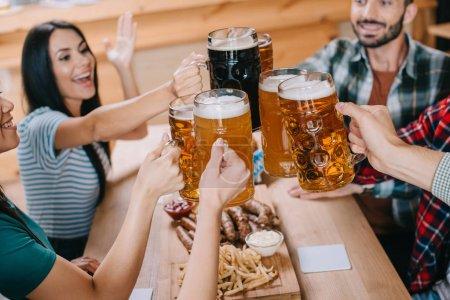 Photo pour Amis joyeux clignotant tasses de bière tout en célébrant octoberfest dans le pub - image libre de droit