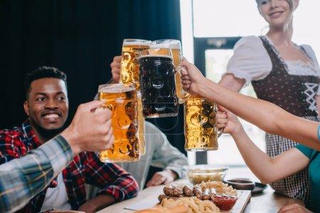 Foto de Alegres amigos multiculturales clinking tazas de cerveza mientras celebra el octoberfest en el pub - Imagen libre de derechos