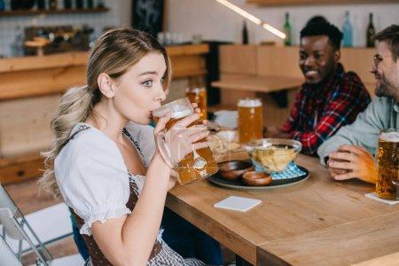 Photo pour Foyer sélectif de jeune femme dans la bière allemande traditionnelle de boire de costume près des amis multiculturels joyeux - image libre de droit
