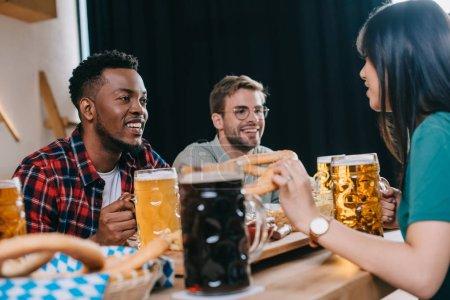 Photo pour Amis multiculturels joyeux s'asseyant près des tasses avec la bière légère et foncée dans le pub - image libre de droit