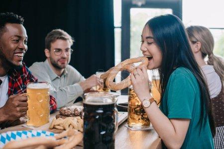 Photo pour Jeune femme asiatique mangeant le bretzel tout en célébrant l'octoberfest avec des amis multiculturels dans le pub - image libre de droit