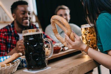 Foto de Vista recortada de la mujer sosteniendo pretzel mientras celebra el octoberfest con amigos multiculturales en el pub - Imagen libre de derechos