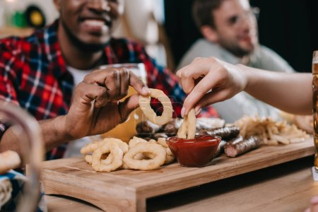 Photo for Cropped view of multicultural friends eating fried onion rings with ketchup in pub - Royalty Free Image