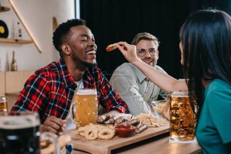 Photo pour Vue de dos de jeune femme alimentant l'homme américain africain avec l'anneau frit d'oignon tout en célébrant l'octoberfest dans le pub - image libre de droit