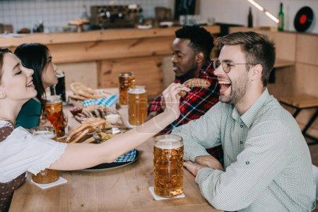 Photo pour Jeune femme alimentant l'homme de sourire avec l'anneau frit d'oignon tout en célébrant l'octoberfest dans le pub avec des amis multiculturels - image libre de droit