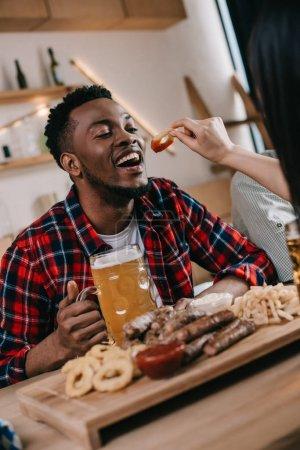 Photo pour Vue recadrée de jeune femme alimentant l'homme américain africain avec l'anneau frit d'oignon tout en célébrant l'octoberfest dans le pub - image libre de droit