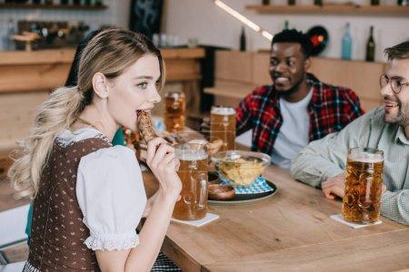 Photo pour Jeune femme mangeant la saucisse frite tout en célébrant l'octoberfest avec les amis multiculturels joyeux - image libre de droit