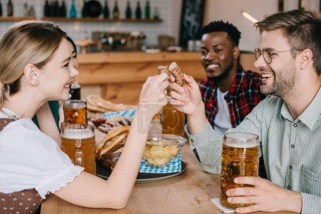 Photo pour Jeune femme et femme retenant la saucisse frite tout en célébrant l'octoberfest avec des amis - image libre de droit