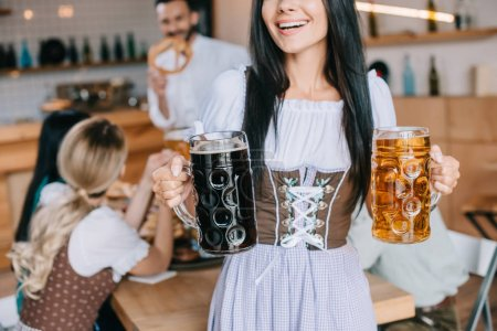 cropped view of waitress in traditional german costume holding mugs of light and dark beer