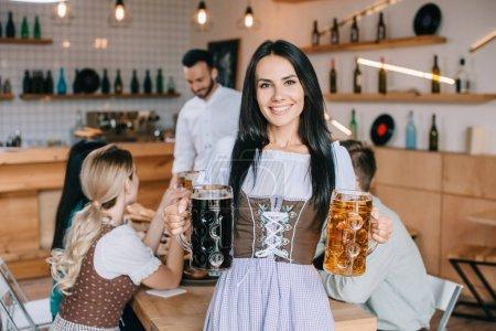 Photo pour Belle serveuse dans le costume allemand traditionnel retenant des tasses de bière légère et foncée et souriant à l'appareil-photo - image libre de droit