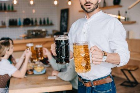 Photo pour Vue partielle du jeune homme tenant des tasses de bière claire et foncée dans un pub - image libre de droit