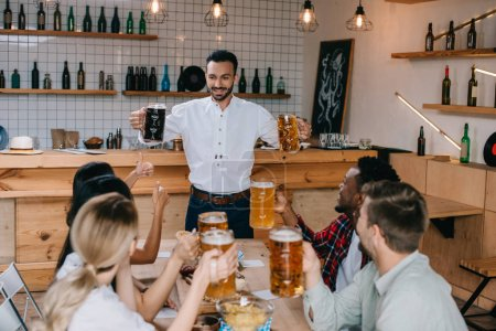 Photo pour Jeune homme gai retenant des tasses de bière légère et foncée dans le pub près des amis multiculturels - image libre de droit