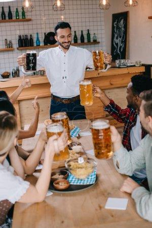 Photo pour Beau jeune homme retenant des tasses de bière légère et foncée dans le pub près des amis multiculturels - image libre de droit
