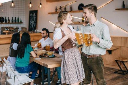 Photo pour Homme et femme joyeux dans les costumes allemands traditionnels retenant des tasses de bière - image libre de droit
