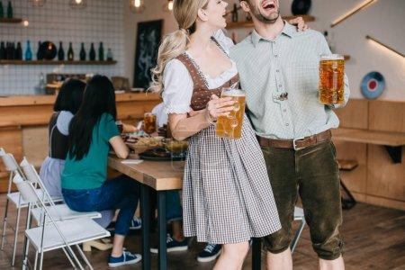 Photo pour Vue recadrée de l'homme et de la femme gais dans les costumes allemands traditionnels retenant des tasses de bière - image libre de droit