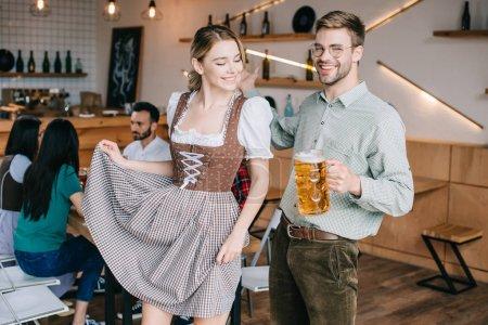 Photo pour Homme et femme heureux dans les costumes allemands traditionnels retenant des tasses de bière - image libre de droit
