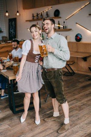 Photo pour Jeune homme et femme dans les costumes allemands traditionnels retenant des tasses de bière - image libre de droit
