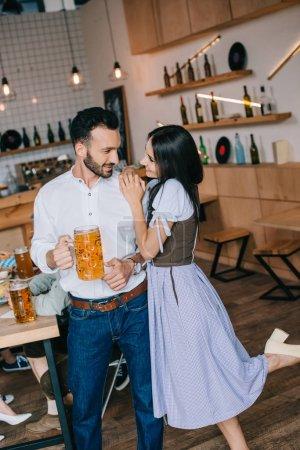 Photo pour Jeune homme souriant retenant le verre de la bière tout en restant près de la belle femme dans le costume allemand traditionnel - image libre de droit
