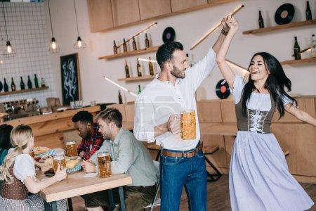 Photo pour Jeune homme beau retenant le verre de la bière tout en dansant avec la belle femme dans le costume allemand traditionnel - image libre de droit