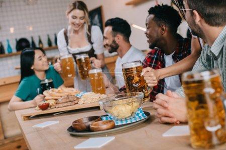 Photo pour Focus sélectif de serveuse dans le costume allemand traditionnel servant de la bière pour des amis multiculturels dans le pub - image libre de droit