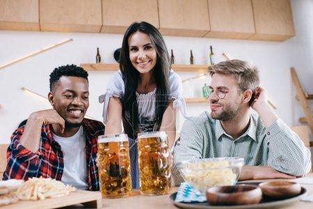 Photo pour Serveuse attirante dans le costume allemand traditionnel servant la bière pour des amis multiculturels dans le pub - image libre de droit