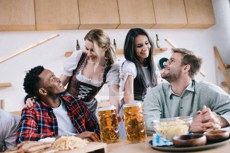 Photo pour Deux serveuses gaies dans les costumes allemands traditionnels servant la bière pour des amis multiculturels dans le pub - image libre de droit