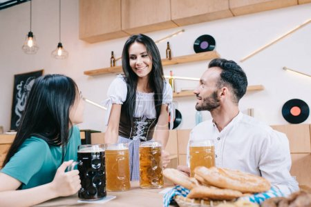 Photo for Cheerful waitress in traditional german costume serving beer for man and woman in pub - Royalty Free Image
