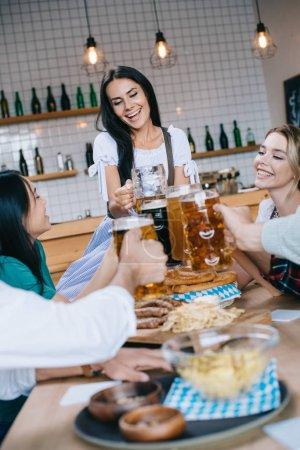 Photo pour Serveuse attirante dans le costume allemand traditionnel retenant le verre de la bière tout en restant près des amis multiculturels célébrant l'octoberfest dans le pub - image libre de droit