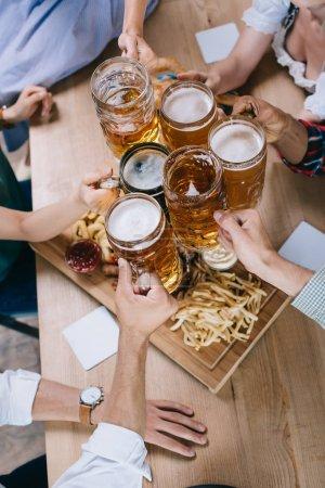 Photo pour Vue recadrée d'amis multiculturels clignotant tasses de bière légère et sombre - image libre de droit