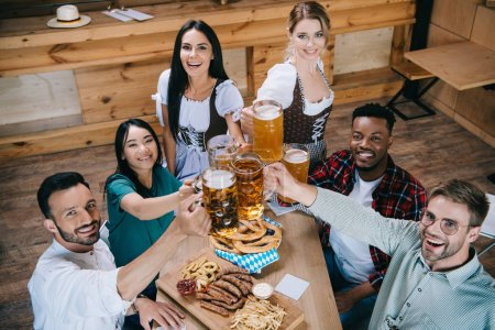 Photo for Attractive waitresses in traditional german costumes clinking mugs of beer with multicultural friends - Royalty Free Image